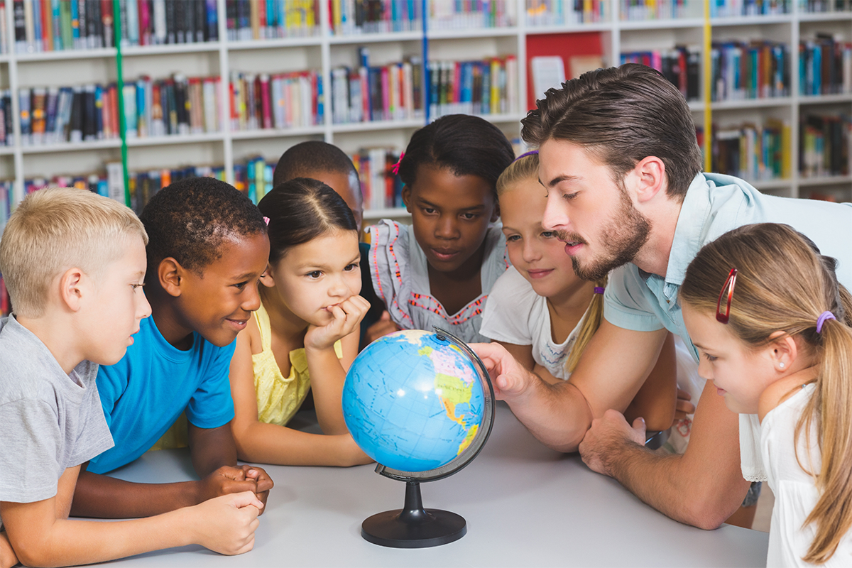 Group of students and teacher looking at a earth globe.